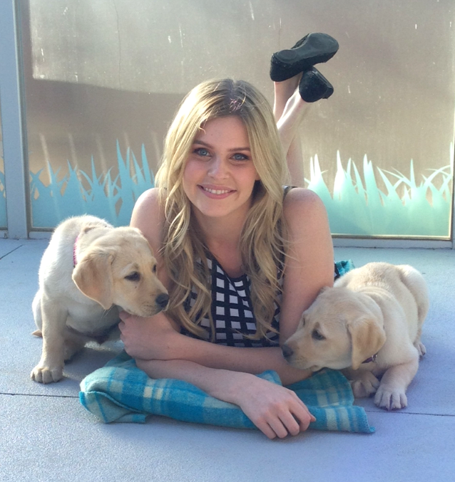 Photo of Jenna with a golden labrador puppy on either side of her
