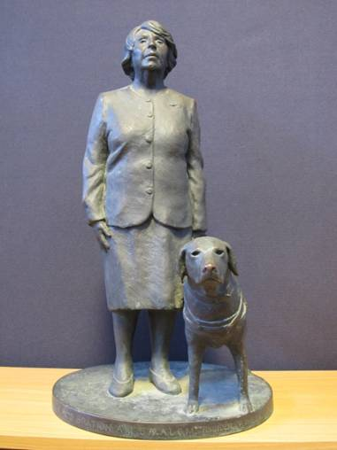 A statue of Mrs P M Gration and a dog sitting next to her