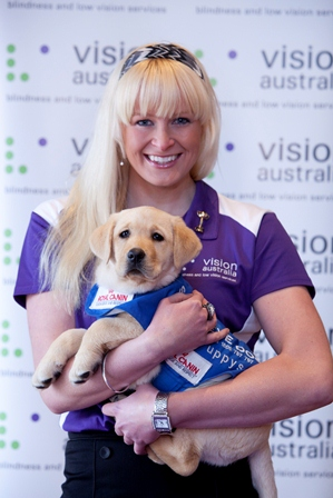 Jess Gallagher smiling and holding a Seeing Eye Dog puppy in front of Vision Australia poster in background.